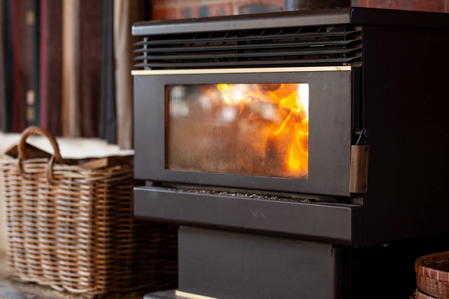 Black Metal Stove Fireplace With A Burning Flame Behind A Glass